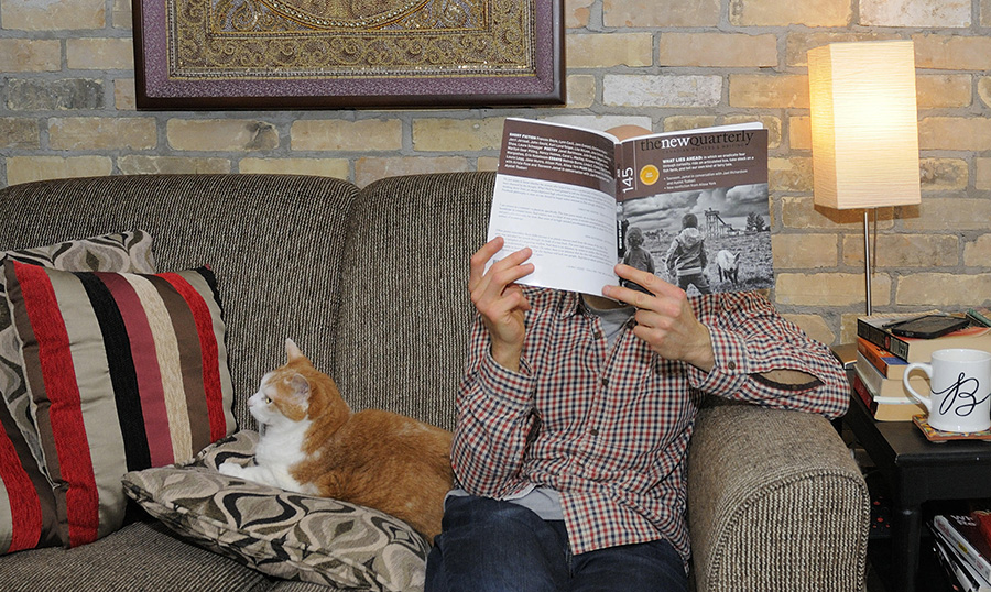 Ron Schafrick's reading space: the author with magazine and cat